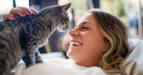 Woman laying down with cat: Wellness Care in Austin